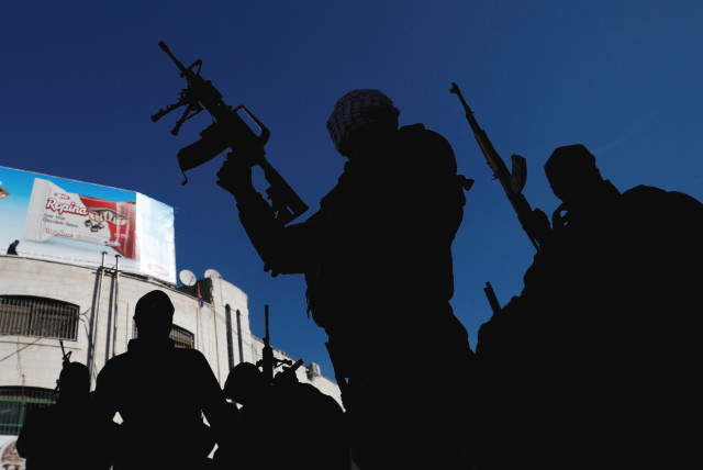 FATAH GUNMEN hold rifles during a demonstration in the West Bank. (photo credit: REUTERS)
