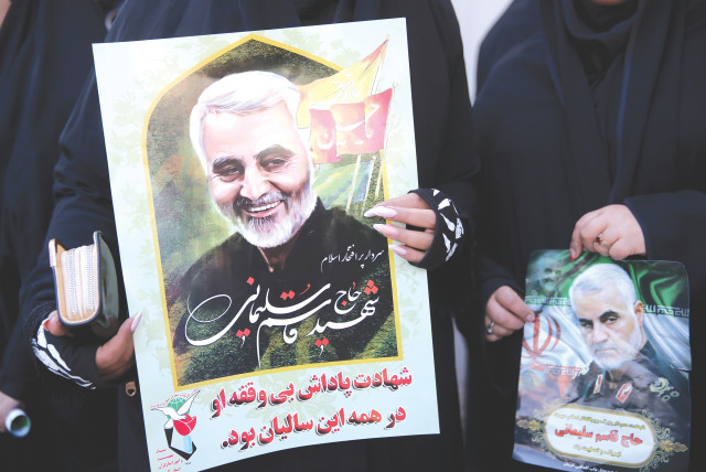 WOMEN HOLD pictures of Iranian Maj.-Gen. Qasem Soleimani during a funeral procession and burial at his hometown in Kerman (photo credit: MEHDI BOLOURIAN/FARS NEWS AGENCY/WANA (WEST ASIA N)