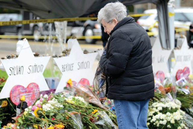 A visitor views a makeshift memorials outside the Tree of Life synagogue  in Pittsburgh, in 2018. (photo credit: ALAN FREED/REUTERS)