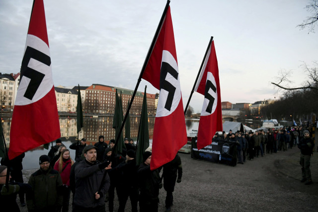 Finnish neo-nazis start their Independence Day march with swastika flags in Helsinki, Finland December 6, 2018. (photo credit: MARTTI KAINULAINEN/LEHTIKUVA/VIA REUTERS)