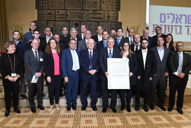 President Reuven Rivlin surrounded by the signatories who convened at the President's Residence on Sunday, to sign an anti-racism pact initiated by Israelis Against Racism, February 2, 2020 (photo credit: MARK NEYMAN/GPO)