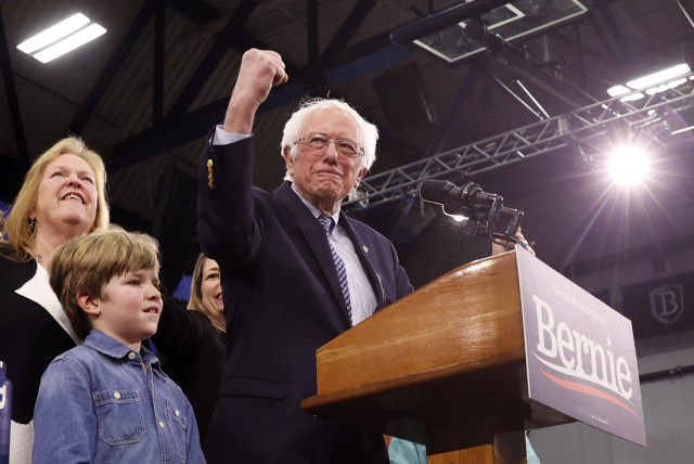 Democratic U.S. presidential candidate Senator Bernie Sanders is accompanied by his wife Jane O'Meara Sanders and other relatives as he speaks at his New Hampshire primary night rally in Manchester, N.H., U.S., February 11, 2020 (photo credit: REUTERS/MIKE SEGAR)