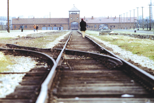 VISITORS WALK along the railway track at the main gate of the Auschwitz Birkenau concentration camp. (photo credit: REUTERS)
