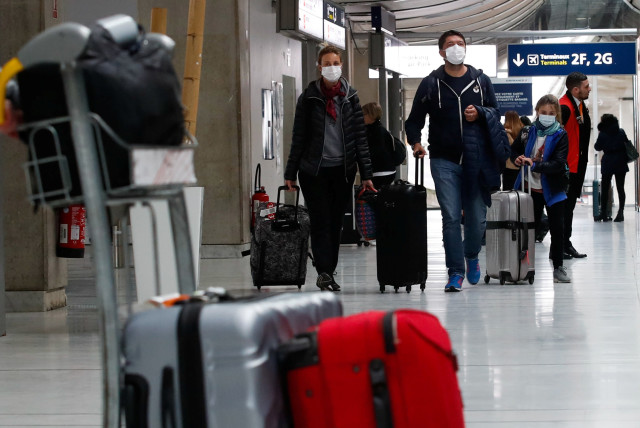 People wearing protective face masks arrive at Charles de Gaulle airport near Paris, France. (photo credit: REUTERS/GONZALO FUENTES)