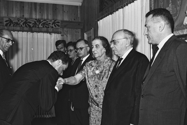 GERMAN AMBASSADOR Rolf Pauls kisses the hand of foreign minister Golda Meir, after presenting his credentials at the President's Residence in Jerusalem in 1965. (photo credit: MOSHE PRIDAN / GPO)