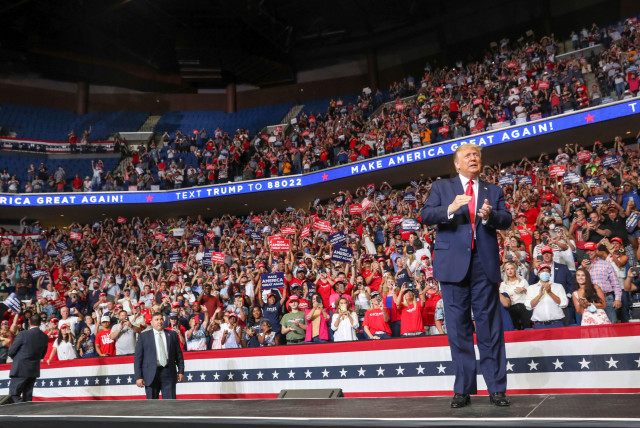 U.S. President Donald Trump reacts to the crowd as he arrives onstage at his first re-election campaign rally in several months in the midst of the coronavirus disease (COVID-19) outbreak, at the BOK Center in Tulsa, Oklahoma, U.S., June 20, 2020 (photo credit: REUTERS/LEAH MILLIS)