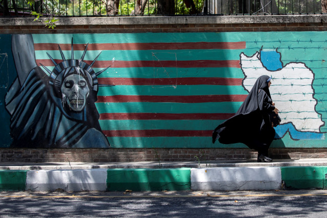 A woman walks past the mural showing U.S. flag with barbed wire and the Statue Of Liberty with skull face in Tehran, Iran June 25, 2019. (photo credit: REUTERS)