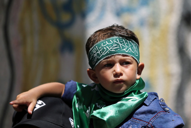 Un garçon palestinien portant un bandeau du Hamas participe à une manifestation contre le projet israélien d'annexer des parties de la Cisjordanie occupée, dans le sud de la bande de Gaza, le 26 juin 2020 (crédit photo: IBRAHEEM ABU MUSTAFA / REUTERS)