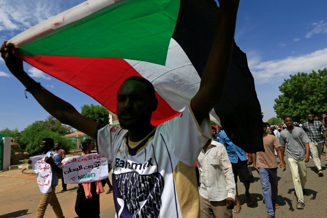 A Sudanese protester carries their national flag as they march in a demonstration to mark the anniversary of a transitional power-sharing deal with demands for quicker political reforms in Khartoum, Sudan August 17, 2020 (photo credit: REUTERS/MOHAMED NURELDIN ABDALLAH)