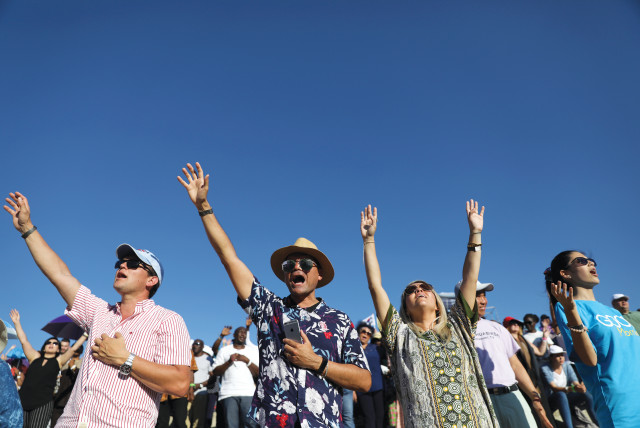 EVANGELICAL CHRISTIAN pilgrims and tourists reach for the sky at a 2019 religious retreat in Nazareth (photo credit: AMMAR AWAD/REUTERS)