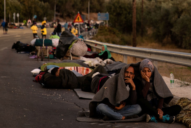 Couple sits covered with a blanket as refugees and migrants camp on a road following a fire at the Moria camp on the island of Lesbos (photo credit: REUTERS)