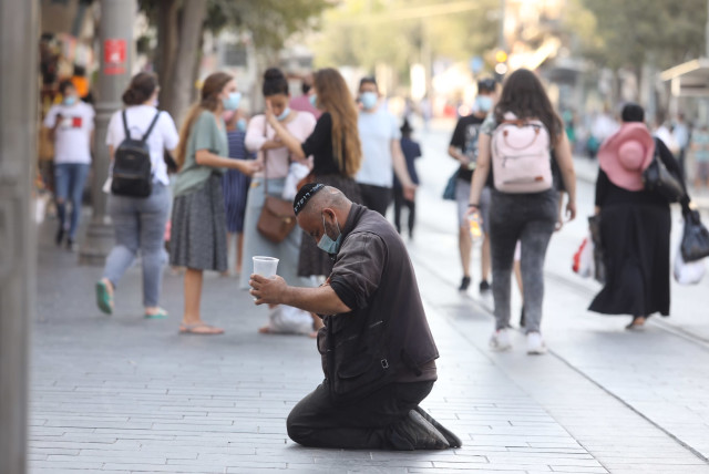 A beggar sits and asks for money amid the coronavirus crisis, Jerusalem, 2020 (photo credit: MARC ISRAEL SELLEM)