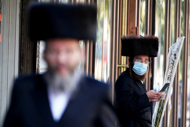 ULTRA-ORTHODOX men – one masked, one not – are seen in the haredi enclave of Borough Park in Brooklyn, New York, on October 6.  (photo credit: CARLO ALLEGRI/REUTERS)