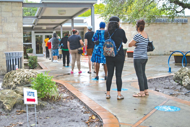Floridians stand in line to vote on first day of early voting for the general election in Miami, on Monday. (photo credit: DAVID SANTIAGO/MIAMI HERALD/TNS)