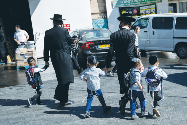 A FATHER walks his children home from school in Jerusalem on Sunday. (photo credit: YONATAN SINDEL/FLASH 90)