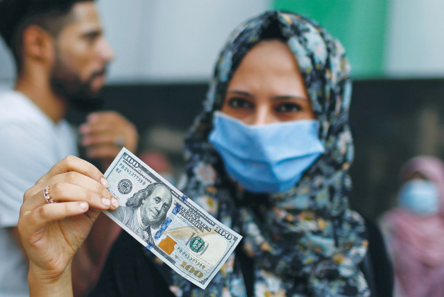 A WOMAN shows a $100 bill she received as aid from Qatar, during a lockdown amid the coronavirus outbreak in Gaza City in September.  (photo credit: MOHAMMED SALEM/ REUTERS)