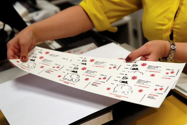 "An employee of the Austrian postal service holds a sheet of so-called ""corona stamps"" in a post office, as the 2.75 euro ""corona stamp"" is printed on three-ply toilet paper and sold individually as part of a 10 cm wide sheet, in Vienna, Austria October 23, 2020.  (photo credit: REUTERS)"