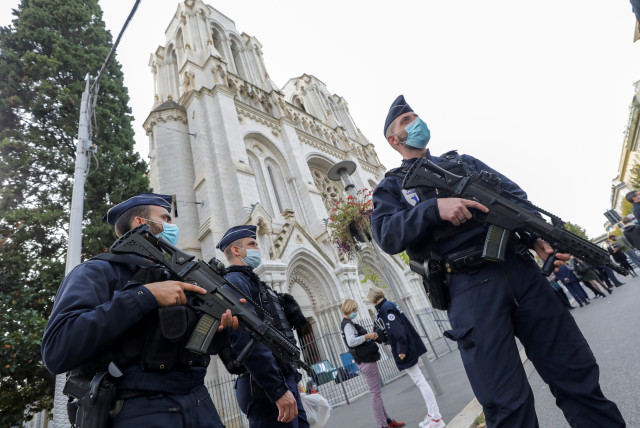 Police officers stand near Notre Dame church, where a knife attack took place, in Nice, France October 29, 2020. (photo credit: REUTERS/ERIC GAILLARD)