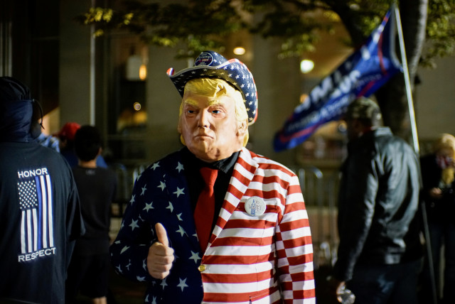 A supporter of US President Donald Trump dressed with the US flag colors and a mask depicting Trump gives a thumbs up as votes continue to be counted. November 6, 2020 (photo credit: EDUARDO MUNOZ / REUTERS)
