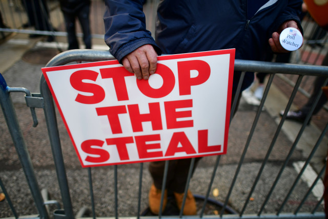 """A supporter of President Donald Trump holds a sign stating """"STOP THE STEAL"""" and a pin stating """"Poll Watcher"""" after Democratic presidential nominee Joe Biden overtook President Donald Trump in the Pennsylvania general election vote count across the street from where ballots are being counted, three d (photo credit: REUTERS)"""