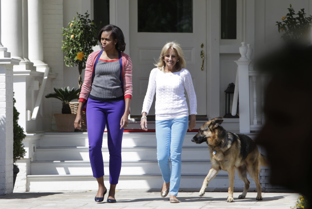 U.S. First Lady Michelle Obama (L) and Jill Biden, wife of Vice President Joe Biden, walk out with Biden's family dog Champ to host a Joining Forces Service event at the Naval Observatory in Washington May 10, 2012. (photo credit: YURI GRIPAS/REUTERS)