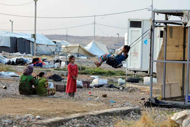 A girl plays on a makeshift swing at Hammam Al-Alil camp where displaced Iraqis prepare to be evacuated, south of Mosul (photo credit: REUTERS)