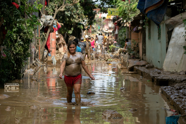 A woman wades through muddy floodwater following Typhoon Vamco, in San Mateo, Rizal province, Philippines, November 13, 2020.  (photo credit: REUTERS/ELOSIA LOPEZ)