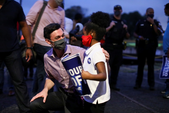 Democratic US Senate candidate Jon Ossoff greets a supporter after speaking at a campaign event at the Georgia State Railroad Museum in Savannah, Georgia, US November 12, 2020. (photo credit: REUTERS/DUSTIN CHAMBERS)