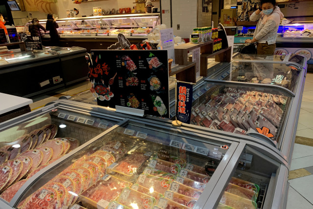 Woman checks imported frozen meat at a supermarket in Beijing (photo credit: REUTERS)