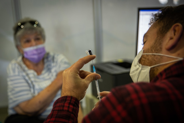 An Israeli woman receives a coronavirus vaccine in Jerusalem. (photo credit: YONATAN SINDEL/FLASH90)