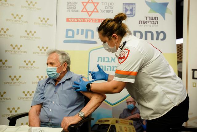 An MDA volunteer vaccinates an elderly man against the novel coronavirus. (photo credit: MDA)
