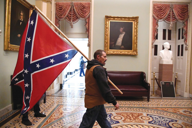 A SUPPORTER of Donald Trump carries a Confederate battle flag through the US Capitol in Washington, DC, on Wednesday. (photo credit: MIKE THEILER/REUTERS)