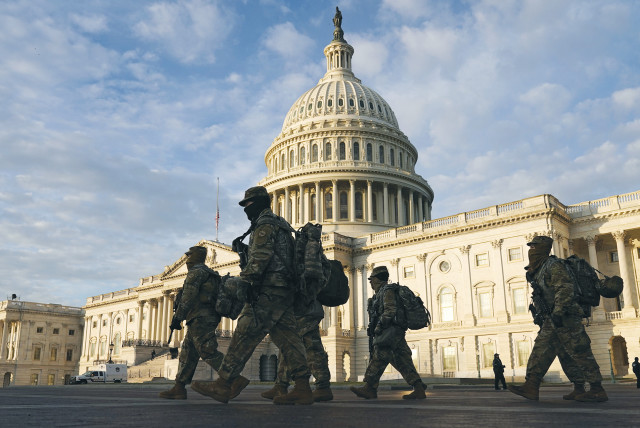 NATIONAL GUARD members walk in front of the US Capitol on Thursday, as tension continues ahead of President-elect Joe Biden's inauguration next week. (photo credit: JOSHUA ROBERTS / REUTERS)