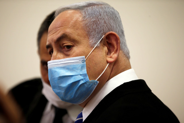 Israeli Prime Minister Benjamin Netanyahu, wearing a face mask, looks on while standing inside the court room as his corruption trial opens at the Jerusalem District Court  May 24, 2020. (photo credit: RONEN ZVULUN/REUTERS)