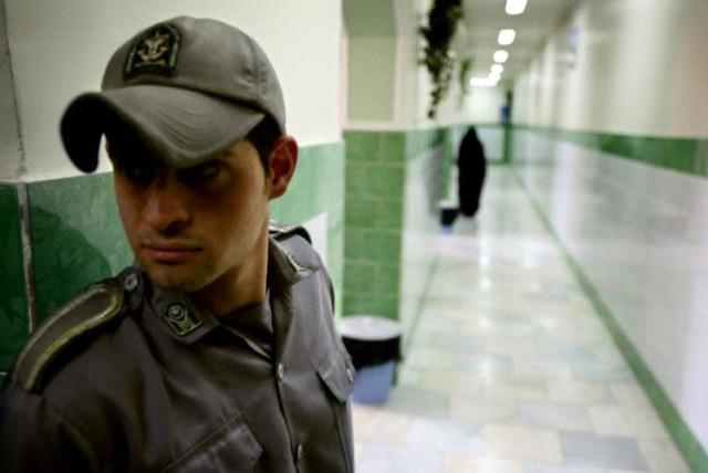 A prison guard stands along a corridor in Tehran's Evin prison June 13, 2006. (photo credit: REUTERS)