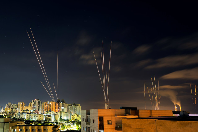 Streaks of light are seen as rockets are launched from the Gaza Strip towards central Israel as seen from Ashkelon, Israel May 16, 2021. (photo credit: AMIR COHEN/REUTERS)