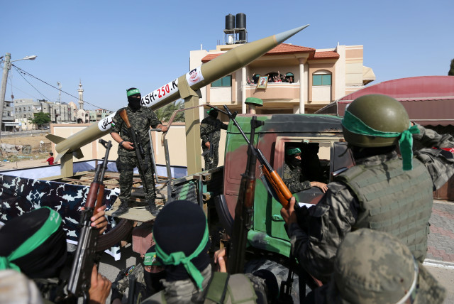 Members of Hamas ride on a truck as they display a rocket during an anti-Israel rally in Rafah, in the southern Gaza Strip May 28, 2021 (photo credit: REUTERS/IBRAHEEM ABU MUSTAFA)