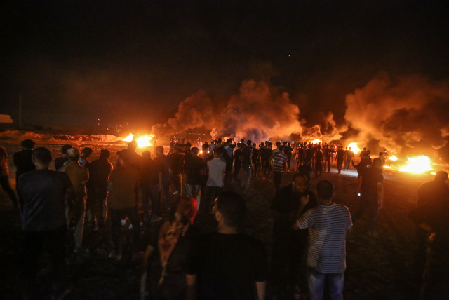 Palestinians protest at night time near the border with Israel, east of Gaza City, on August 28, 2021.  (photo credit: ATIA MOHAMMED/FLASH90)
