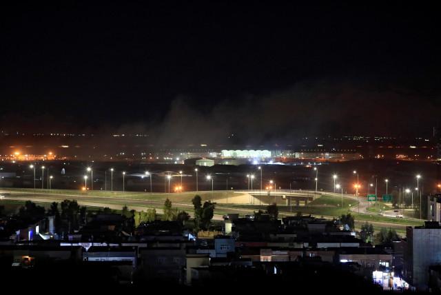 Smoke rises over the Erbil, after reports of mortar shells landing near Erbil airport, Iraq February 15, 2021 (Illustrative).  (photo credit: THAIER AL-SUDANI/REUTERS)