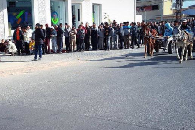 Gazan citizens line up to receive their Qatari grant for humanitarian aid