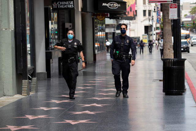 LAPD Officers wear face masks as they patrol Hollywood Blvd during the outbreak of the coronavirus disease (COVID-19), in Los Angeles, California, U.S., May 18, 2020.
