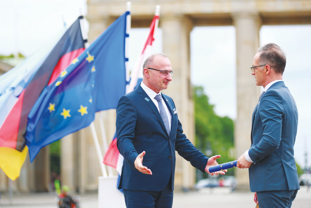 GERMAN FOREIGN Minister Heiko Maas (right) takes over the rotating presidency of the Council of the European Union from Croatian Foreign Minister Gordan Grlic-Radman during a symbolic handover in front of the Brandenburg Gate in Berlin last week.