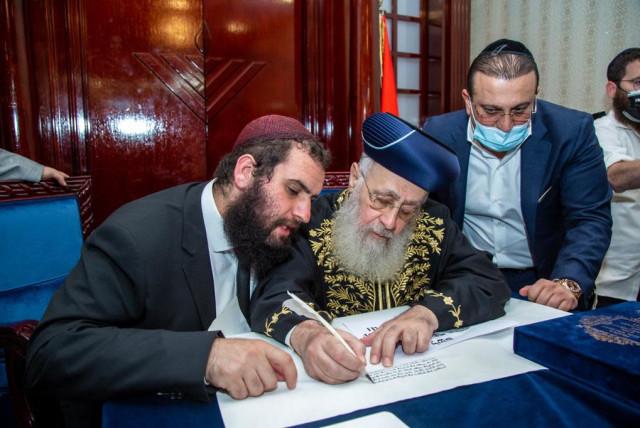 Israeli Chief Rabbi Yitzhak Yosef, center, writes part of a Torah scroll at the Jewish community center in Dubai, Dec. 19, 2020. At left is the center's leader, Rabbi Levi Duchman.