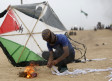 Palestinians prepare an incendiary device attached to a kite before trying to fly it over the border