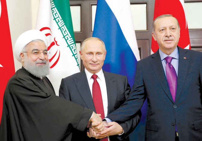 PRESIDENT HASSAN ROUHANI of Iran (left) joins hands with Russian President Vladimir Putin (center) and Turkey's President Tayyip Erdogan in Sochi, Russia (Reuters)