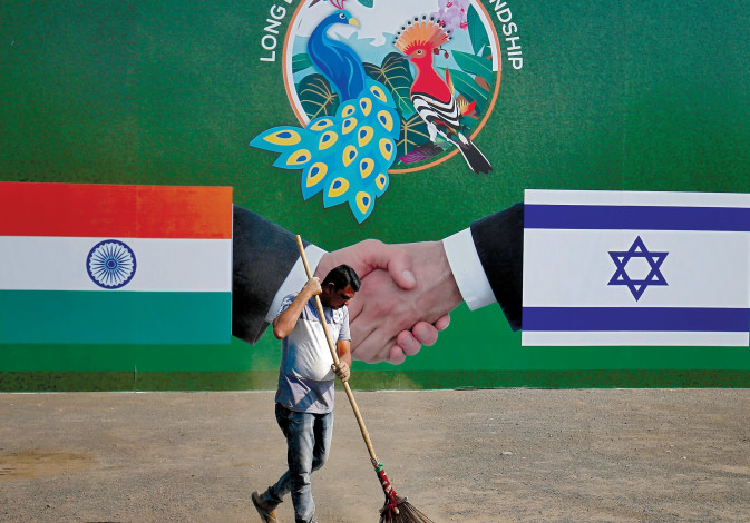 A municipal worker cleans the street in front of a bilboard displaying Indian and Israeli flags for