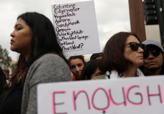 An attendee holds a sign with a list of school shootings during