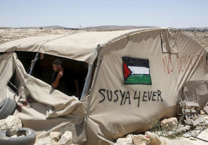 A Palestinian man looks out of a tent in Sussiya village, south of the West Bank city of Hebron