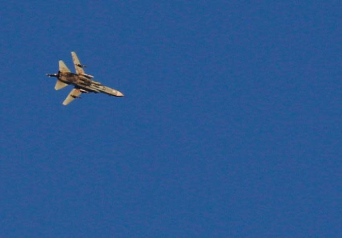 A war jet flies above Syria near the Israeli Syrian border as it is seen from the Golan Heights