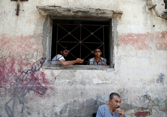 Palestinians look out of their home at Al-Shati refugee camp in Gaza City September 3, 2018